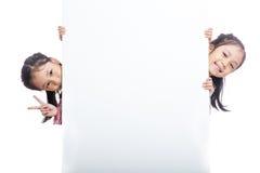 Ασιατικές δίδυμες αδελφές που κρυφοκοιτάζουν πίσω από τον κενό πίνακα διαφημίσεων Στοκ φωτογραφία με δικαίωμα ελεύθερης χρήσης