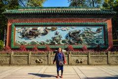 """Ασιατικές ανώτερες γυναίκες με τον κινεζικό δράκο δύο στον μπλε τοίχο """"στον προγονικό ναό """" στοκ φωτογραφία με δικαίωμα ελεύθερης χρήσης"""