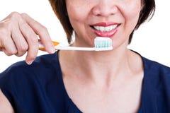 Ασιατικές γυναίκες με τα όμορφα δόντια που κρατούν την οδοντόβουρτσα και τα toothpas Στοκ Φωτογραφίες