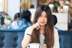 Ασιατικές γυναίκες που κάθονται στη βιβλιοθήκη με το φλιτζάνι του καφέ για να κάνει μια ιδέα Στοκ Φωτογραφία