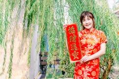 Ασιατικές γυναίκες στα εορταστικά κοστούμια που παρουσιάζουν κόκκινα couplets με τα κινέζικα στοκ φωτογραφίες με δικαίωμα ελεύθερης χρήσης