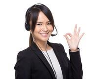 Ασιατικές θηλυκές εξυπηρετήσεις πελατών με το εντάξει σημάδι Στοκ Εικόνες