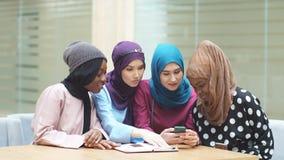 Ασιατικές ισλαμικές γυναίκες που μοιράζονται τις πληροφορίες από το smartphone κατά τη διάρκεια της επίσκεψής τους ένα σεμινάριο φιλμ μικρού μήκους
