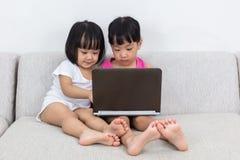 Ασιατικές κινεζικές μικρές αδελφές που παίζουν τον υπολογιστή Στοκ Εικόνες