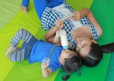 Ασιατικές κορίτσι και μητέρα παιδιών που βρίσκονται στο στρώμα και την κάρτα λάμψης παιχνιδιού για τη σωστή ανάπτυξη εγκεφάλου στ Στοκ Φωτογραφία
