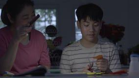 Ασιατικές μητέρες Βοηθώντας τον γιο μου να κάνει τέχνη χρησιμοποιώντας το φως του τηλεφώνου Για να τελειώσει τη δουλειά απόθεμα βίντεο
