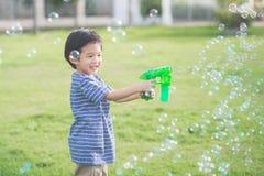 Ασιατικές φυσαλίδες πυροβολισμού παιδιών από το πυροβόλο όπλο φυσαλίδων Στοκ Εικόνες