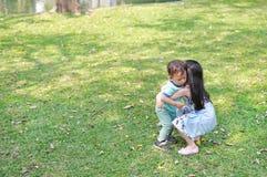 Ασιατική αδελφή που φέρνει την λίγος αδελφός στον κήπο υπαίθριο στοκ εικόνες
