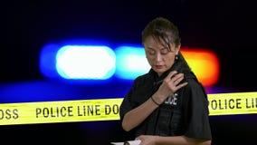Ασιατική αμερικανική αστυνομικίνα που κάνει τις σημειώσεις και που χρησιμοποιεί το ραδιόφωνο αστυνομίας απόθεμα βίντεο