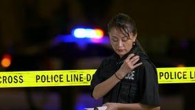 Ασιατική αμερικανική αστυνομικίνα που κάνει τις σημειώσεις και που χρησιμοποιεί το ραδιόφωνο αστυνομίας φιλμ μικρού μήκους
