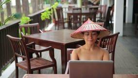 Ασιατική ανεξάρτητη επιχειρησιακή γυναίκα στον καφέ με το lap-top και το τηλέφωνο φιλμ μικρού μήκους