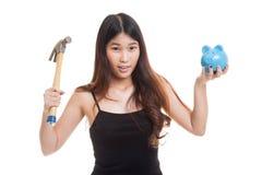 Ασιατική γυναίκα με την τράπεζα και το σφυρί νομισμάτων χοίρων Στοκ Εικόνα
