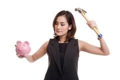 Ασιατική γυναίκα με την τράπεζα και το σφυρί νομισμάτων χοίρων Στοκ Εικόνες