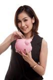 Ασιατική γυναίκα με την τράπεζα νομισμάτων και νομισμάτων χοίρων Στοκ φωτογραφία με δικαίωμα ελεύθερης χρήσης