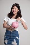 Ασιατική γυναίκα με την τράπεζα νομισμάτων και νομισμάτων χοίρων Στοκ φωτογραφίες με δικαίωμα ελεύθερης χρήσης