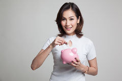 Ασιατική γυναίκα με την τράπεζα νομισμάτων και νομισμάτων χοίρων Στοκ Εικόνα