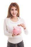 Ασιατική γυναίκα με την τράπεζα νομισμάτων και νομισμάτων χοίρων Στοκ Εικόνες