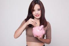 Ασιατική γυναίκα με την τράπεζα νομισμάτων και νομισμάτων χοίρων Στοκ εικόνα με δικαίωμα ελεύθερης χρήσης