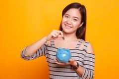 Ασιατική γυναίκα με την τράπεζα νομισμάτων και νομισμάτων χοίρων Στοκ εικόνες με δικαίωμα ελεύθερης χρήσης