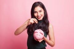 Ασιατική γυναίκα με την τράπεζα νομισμάτων και νομισμάτων χοίρων Στοκ Φωτογραφία
