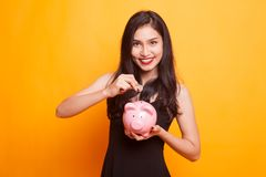 Ασιατική γυναίκα με την τράπεζα νομισμάτων και νομισμάτων χοίρων Στοκ Φωτογραφίες