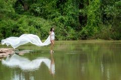 Ασιατική γυναίκα με το άσπρο φόρεμα που χαλαρώνει και που στέκεται στον τροπικό εξωτικό ποταμό με το τυρκουάζ καταπληκτικό νερό χ Στοκ Εικόνες