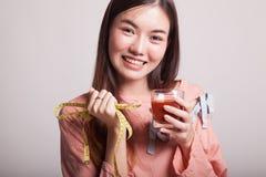 Ασιατική γυναίκα με το χυμό και τη μέτρηση ντοματών της ταινίας Στοκ φωτογραφία με δικαίωμα ελεύθερης χρήσης