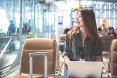 Ασιατική γυναίκα ομορφιάς χρησιμοποιώντας το lap-top και εξετάζοντας έξω τον αερολιμένα Συνεδρίαση γυναικών στο τερματικό αερολιμ στοκ φωτογραφία