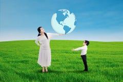 Ασιατική γυναίκα που δίνει τη γη σε ένα παιδί Στοκ εικόνες με δικαίωμα ελεύθερης χρήσης