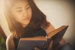Ασιατική γυναίκα που διαβάζει σε ένα βιβλίο το εκλεκτής ποιότητας ύφος Στοκ Φωτογραφίες
