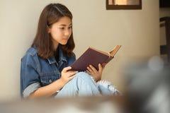 Ασιατική γυναίκα που διαβάζει σε ένα βιβλίο το εκλεκτής ποιότητας ύφος Στοκ Φωτογραφία