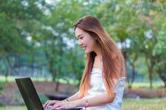 Ασιατική γυναίκα που εργάζεται σε ένα lap-top που χαμογελά σε έναν κήπο ή ένα πάρκο στοκ φωτογραφίες