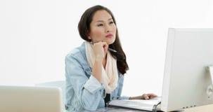 Ασιατική γυναίκα που εργάζεται στο γραφείο που γράφει στο φάκελλο απόθεμα βίντεο
