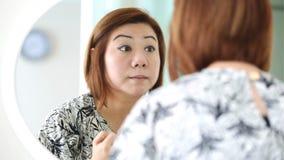 Ασιατική γυναίκα που ισχύει makeup και που εξετάζει τον καθρέφτη στην κρεβατοκάμαρα απόθεμα βίντεο