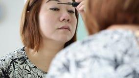 Ασιατική γυναίκα που ισχύει makeup και που εξετάζει τον καθρέφτη στην κρεβατοκάμαρα φιλμ μικρού μήκους