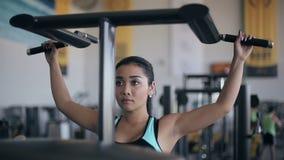 Ασιατική γυναίκα που κάνει τις ασκήσεις στις συσκευές κατάρτισης δύναμης στη γυμναστική φιλμ μικρού μήκους
