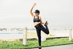 Ασιατική γυναίκα που κάνει τις τεντώνοντας ασκήσεις υπαίθρια κατά μήκος της πόλης sidew στοκ φωτογραφία