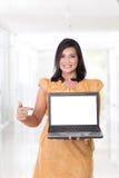 Ασιατική γυναίκα που κρατά ένα ανοικτό lap-top, που δείχνει στο lap-top Στοκ Φωτογραφία