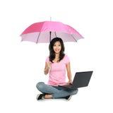 Ασιατική γυναίκα που κρατά μια ομπρέλα και ένα lap-top καθμένος στο θόριο στοκ φωτογραφία με δικαίωμα ελεύθερης χρήσης