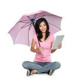 Ασιατική γυναίκα που κρατά μια ομπρέλα και ένα PC ταμπλετών καθμένος επάνω στοκ φωτογραφία με δικαίωμα ελεύθερης χρήσης