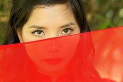 Ασιατική γυναίκα που κρυφοκοιτάζει πέρα από το κόκκινο ύφασμα στοκ φωτογραφία με δικαίωμα ελεύθερης χρήσης