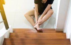 Ασιατική γυναίκα που πέφτει κάτω του σκαλοπατιού, θηλυκό χεριών σχετικά με τα πόδια της που τραυματίζεται Στοκ φωτογραφίες με δικαίωμα ελεύθερης χρήσης