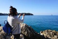 Ασιατική γυναίκα που στέκεται στο βράχο που παίρνει μια φωτογραφία της αδριατικής θάλασσας Στοκ Φωτογραφίες