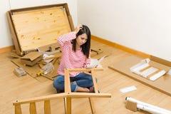 Ασιατική γυναίκα που συγκεντρώνει τη νέα καρέκλα με την οδηγία Στοκ Φωτογραφίες