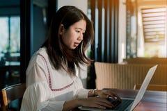 Ασιατική γυναίκα που φορά μια άσπρη συνεδρίαση πουκάμισων μπροστά από έναν φορητό προσωπικό υπολογιστή με την έκφραση που είναι σ στοκ εικόνες