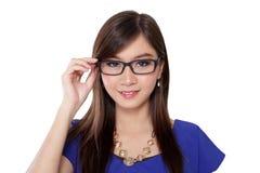 Ασιατική γυναίκα που χαμογελά και που κρατά τα γυαλιά Στοκ φωτογραφία με δικαίωμα ελεύθερης χρήσης