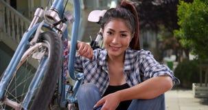 Ασιατική γυναίκα που χαμογελά με το ποδήλατό της στοκ εικόνες