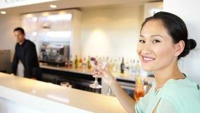 Ασιατική γυναίκα που χαμογελά στη κάμερα που πίνει ένα κοκτέιλ απόθεμα βίντεο
