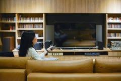 Ασιατική γυναίκα που χρησιμοποιεί έναν τηλεχειρισμό για να ανοίξει τη TV με το κενό scre στοκ εικόνες