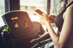 Ασιατική γυναίκα που χρησιμοποιεί το έξυπνο τηλέφωνο όταν workout ή την κατάρτιση δύναμης στοκ εικόνες